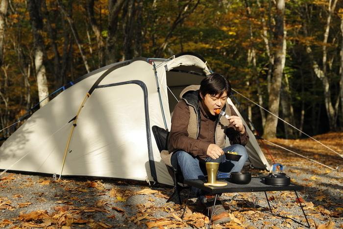 テントサイトで食事をしている男性