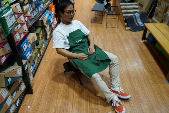 椅子に座るアウトドアショップスタッフ