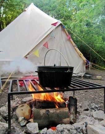 テントの前で薪に火をつけ、ダッチオーブンで調理する様子