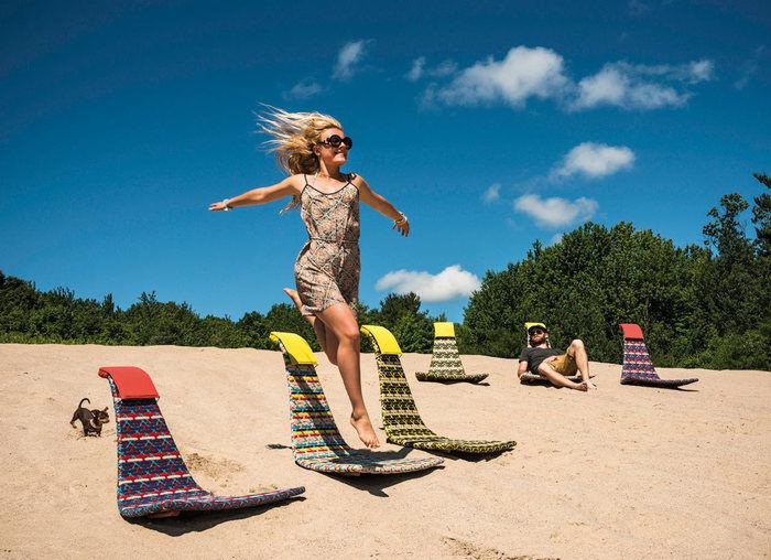 砂浜に置かれたカラフルなロッキングチェア