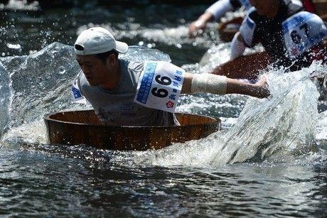 水しぶきを立ててたらいこぎ競争を行う人