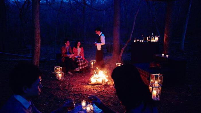焚き火にあたりながらお酒を楽しむ男女