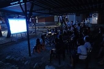 木洩れ日と清流のキャンプ場で映画を見る人たち