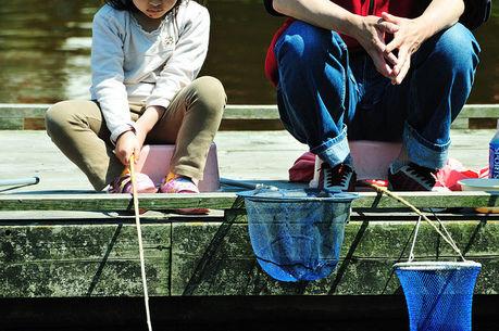 あらかわ遊園魚つり広場で釣りをする親子
