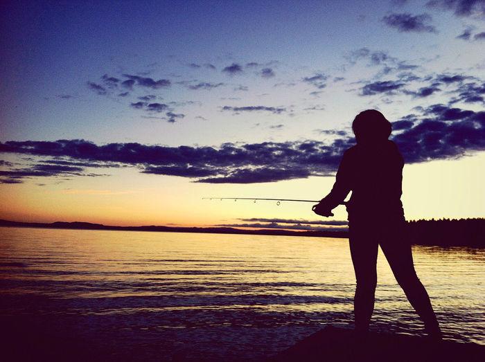 夕暮れ時に釣りをする女性