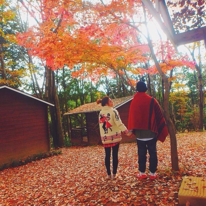 紅葉の下で手をつなぐカップル