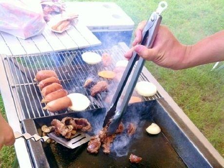 バーベキューコンロで肉を焼いている人