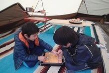 テント内でゲームをする男の子