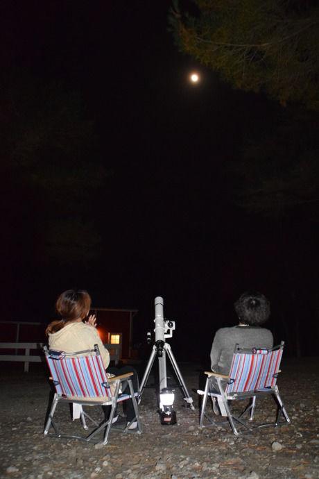 チェアに座り夜空を見上げる人