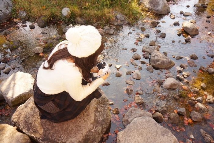 小川の写真をとる女性