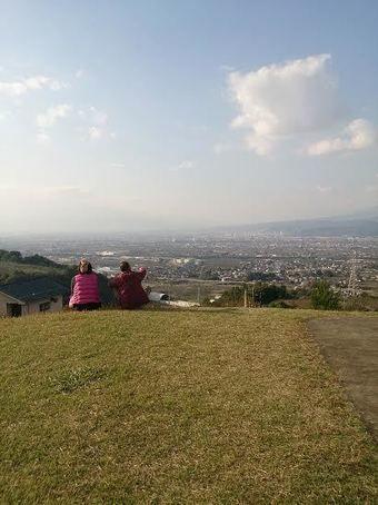 山梨県八代ふるさと公園の古墳から景色をみる人々