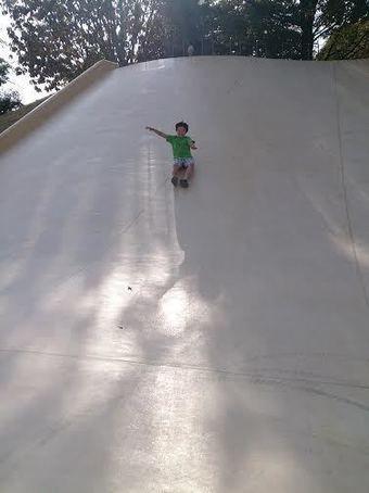 山梨県八代ふるさと公園、わんぱく広場で滑り台をする子供