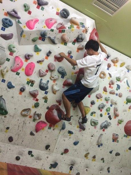 ウォールの高いところを登る男性