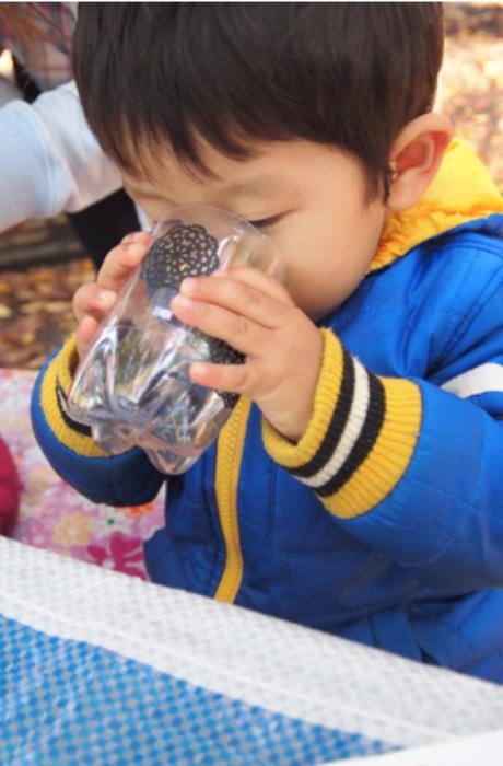 手作りコップで手作り経口補水液を試飲する子供