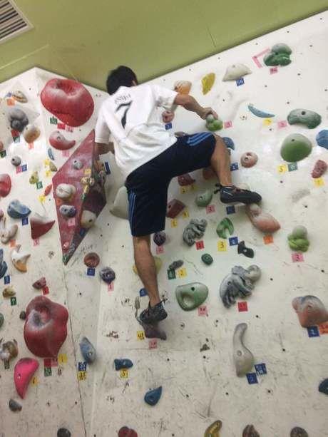 ボルダリングの天辺に登る男性