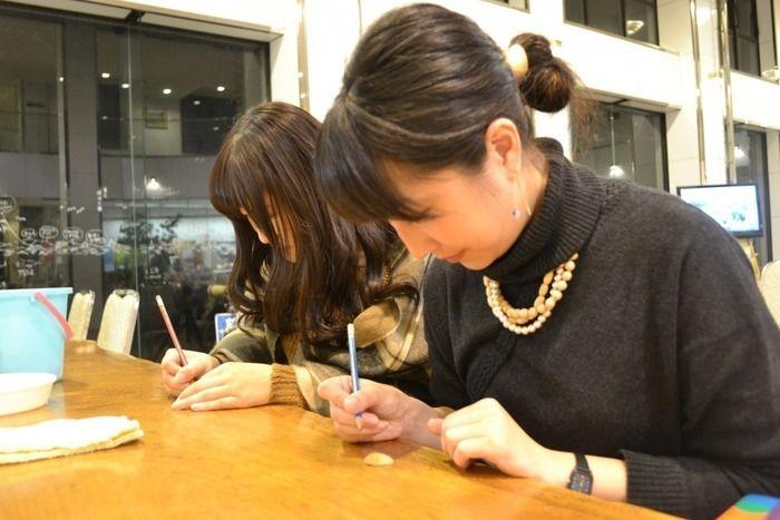 貝殻に文字を書く女性