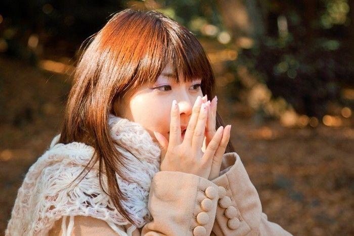 寒そうに手を温めている女性