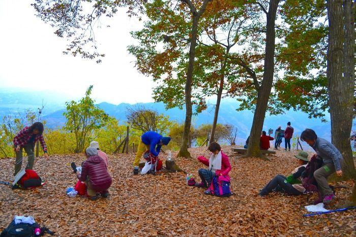 山々に囲まれた山頂でランチを楽しむイベント参加者