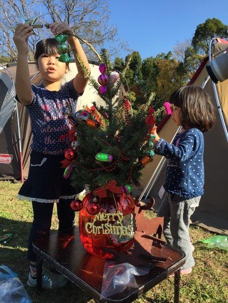 クリスマスツリーに飾りをする子供