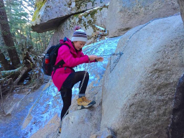鎖を使って険しい崖を進む女性