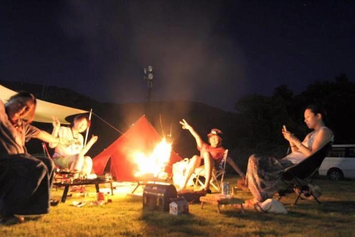 焚き火を囲んでキャンプを楽しむ女性たち