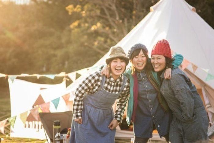 肩を組み笑顔の女性3人とテント