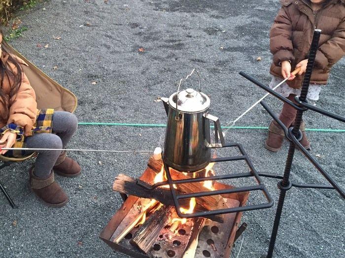 焚き火にかけられたケトルとマシュマロを焼く子供