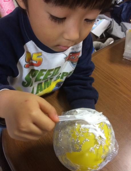 風船にボンドを塗る子供