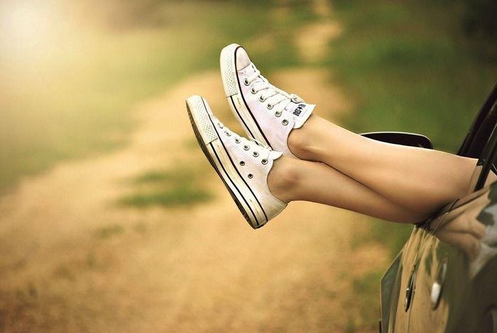 スニーカーを履いた足を車の窓から出している様子