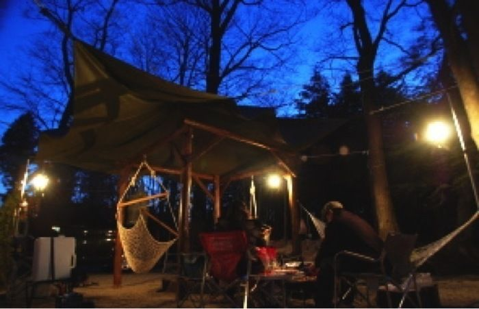 キャンプアンドキャビンズ那須高原でタープにライトをつけてキャンプを楽しむ人