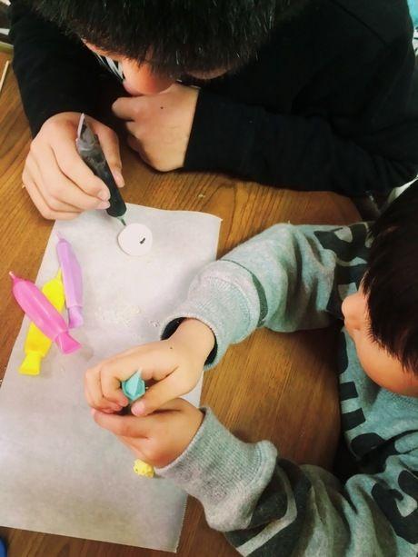 マシュマロにチョコペンで絵を描く子供