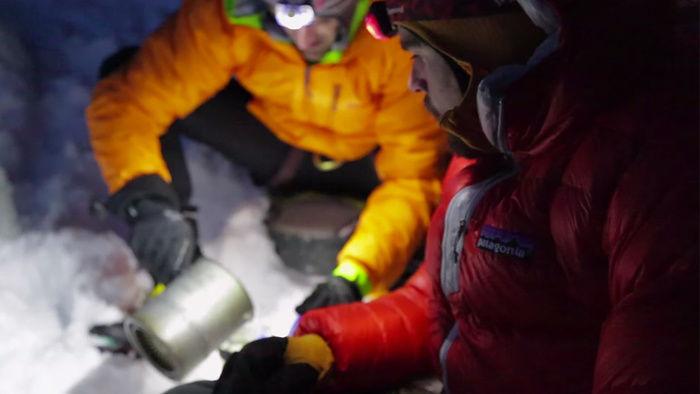 Patagonia(パタゴニア)の100%トレーサブルダウンを着て山登りをする男性