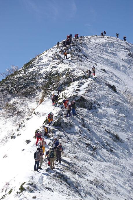 険しい雪山を登る人々
