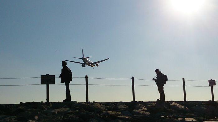 飛ぶ飛行機と飛行機を写真に収める人の影