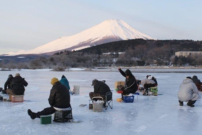 富士山のしたでワカサギ釣りをする人々