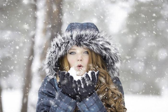 雪を手のひらに乗せて息を吹きかける女性