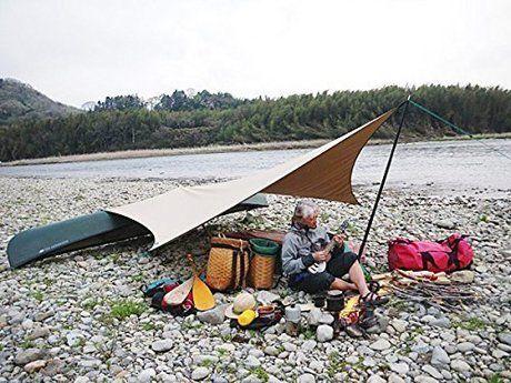 川辺に設置されたタープの下で楽器を演奏する男性