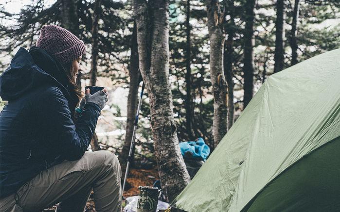 冬キャンプで暖かい飲み物を飲む女性