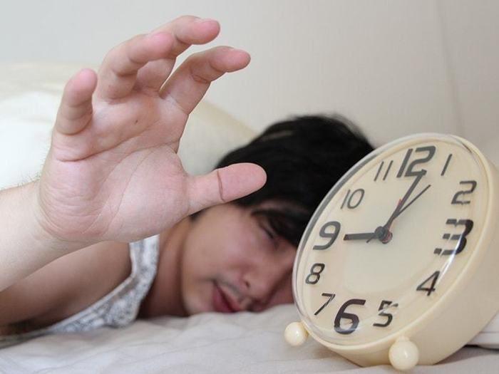 寝起きでめざまし時計をつかもうとする男性