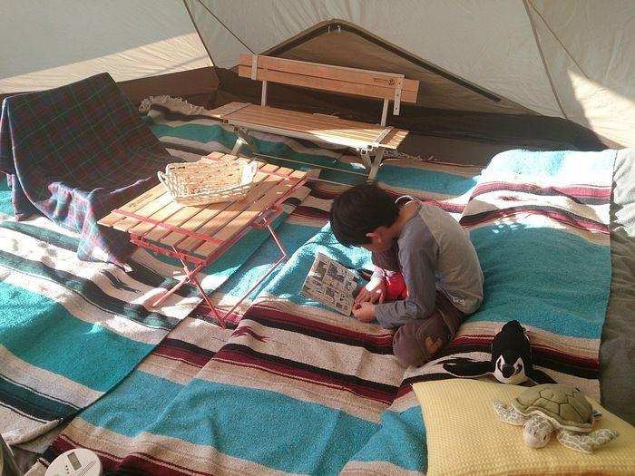 ラグマットの敷かれたテント内で本を読む子供