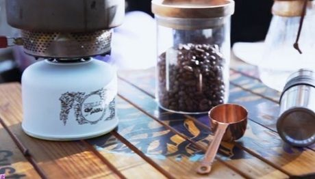 テーブルの上のモンロのガスカートリッジカバーとコーヒー豆
