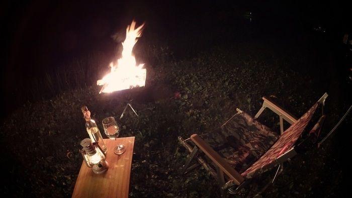 焚火を見ながらお酒を楽しむ夜のソロキャンプの様子