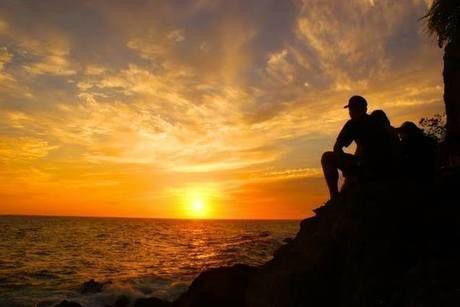 海に沈む夕日をみる人
