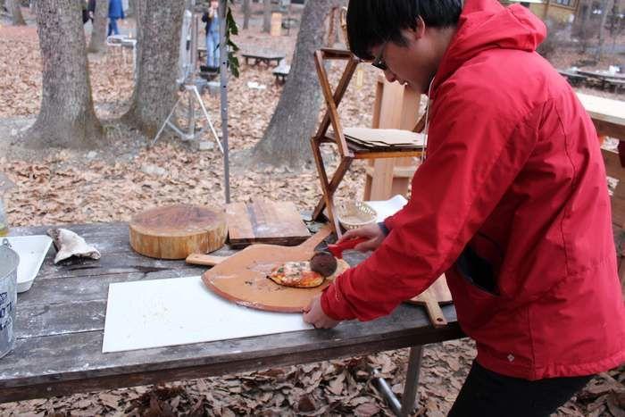 完成したピザを切る男性