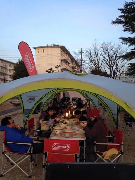 タープの下で夕食を囲む人々