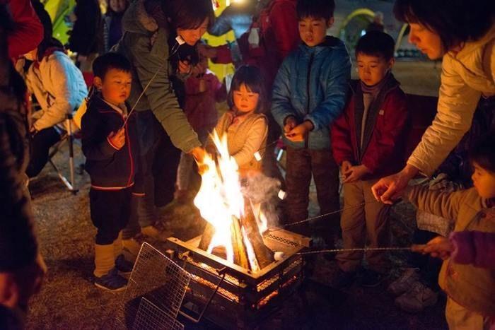 たき火で焼きマシュマロを作る子供