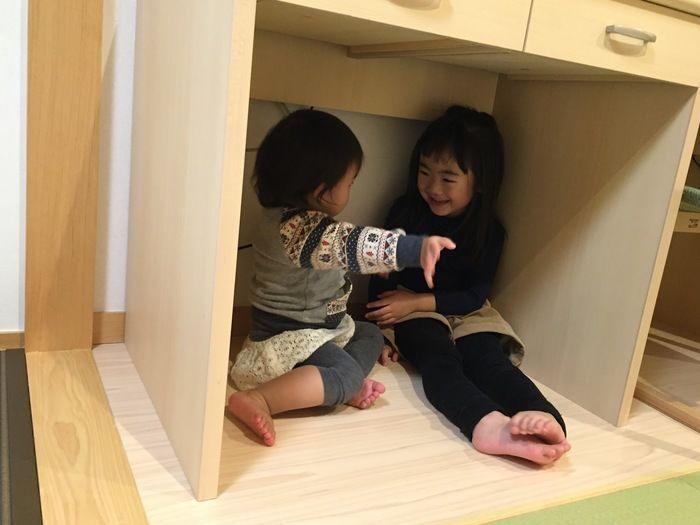 机の下でお話する姉妹