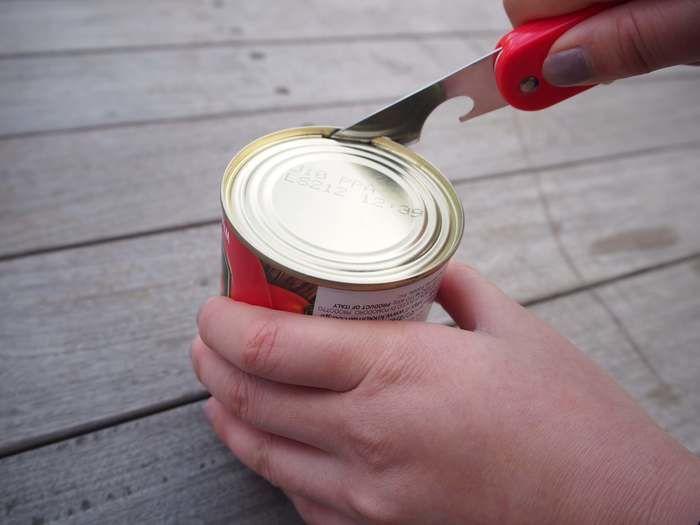 缶詰を缶切りで開けている様子