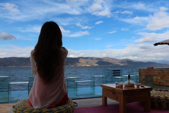 海を眺めている女性の後ろ姿