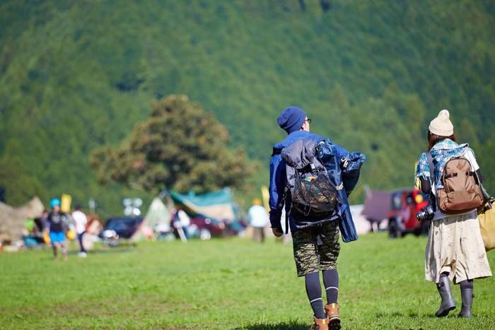 大きなリュックを背負ってキャンプ場を歩く男女
